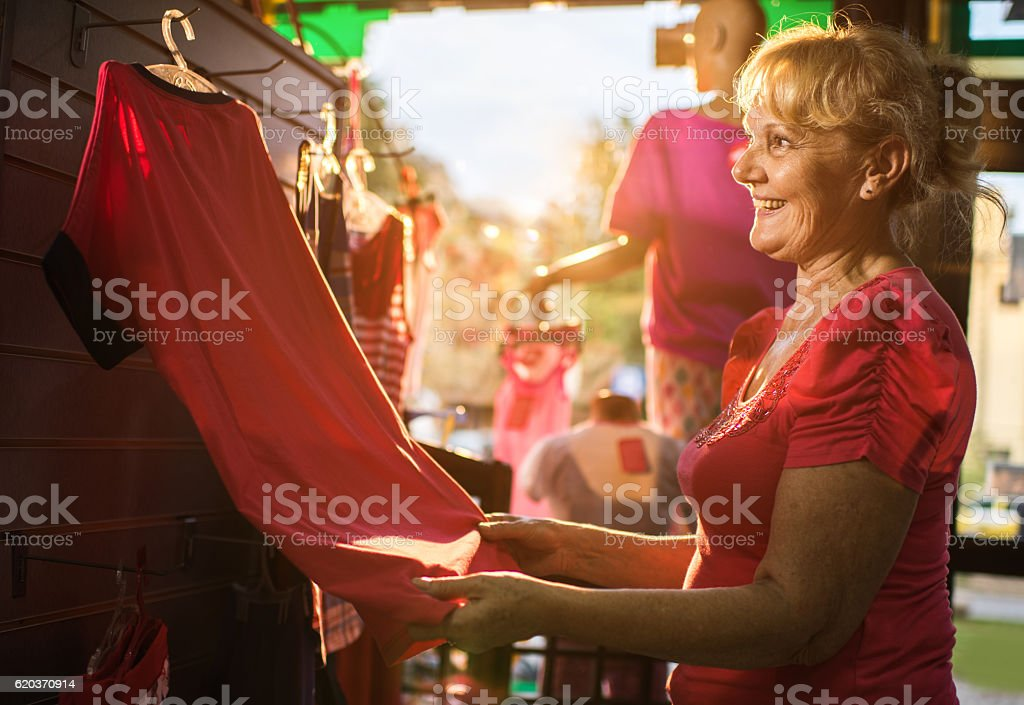 Happy senior woman buying t-shirts in a boutique. foto de stock royalty-free