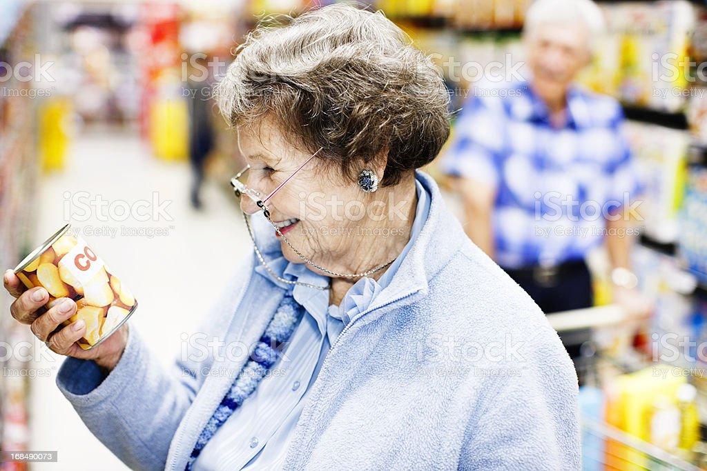 Happy senior woman checks can label in supermarket stock photo
