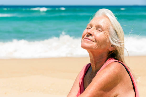 Happy senior woman dreaming on the beach, background with copy space Happy senior woman dreaming on the beach, background with copy space, full frame horizontal composition sunbathing stock pictures, royalty-free photos & images