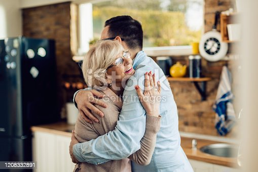 Happy mature woman and her adult son embracing in the kitchen.