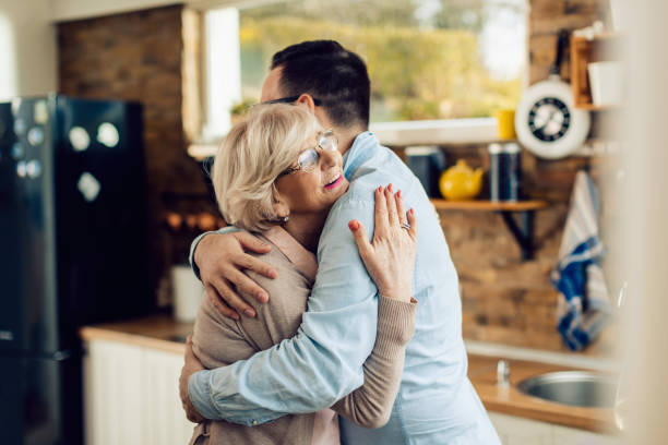 Happy senior woman embracing her adult son in the kitchen. stock photo