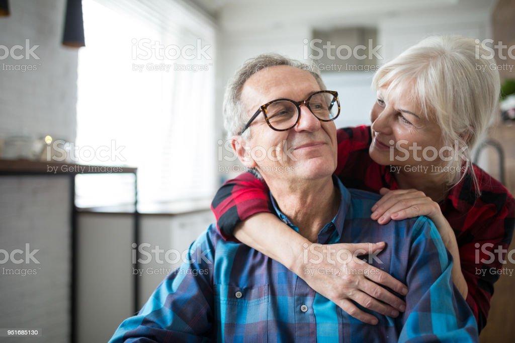 Mujer senior feliz abrazando a su marido foto de stock libre de derechos