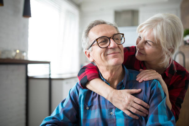 happy senior woman embracing her husband - idosos imagens e fotografias de stock