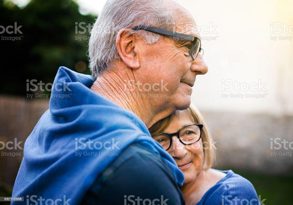 Happy senior woman embracing man in backyard stock photo