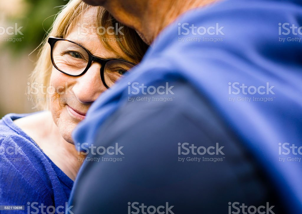 Happy senior woman embracing man outdoors stock photo