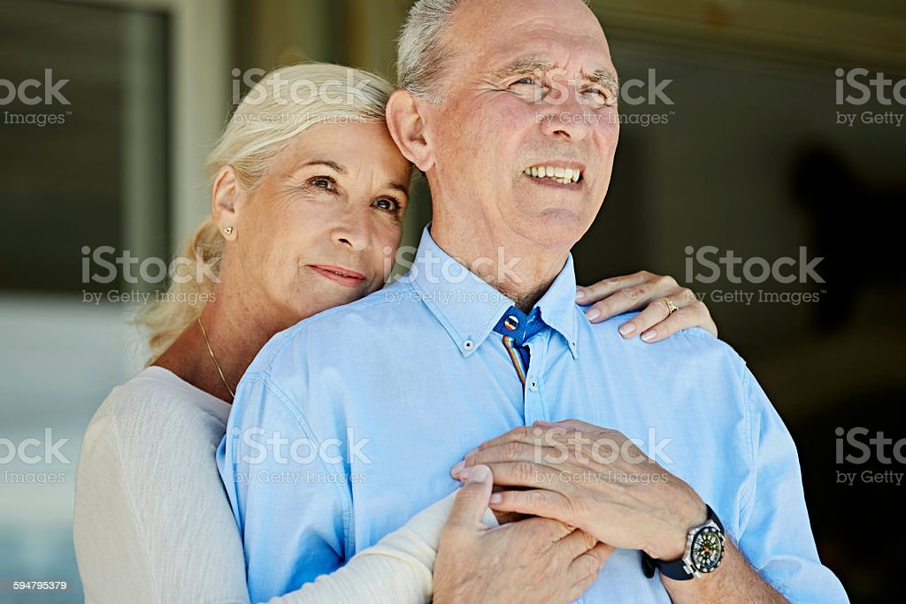 Happy senior woman embracing man stock photo