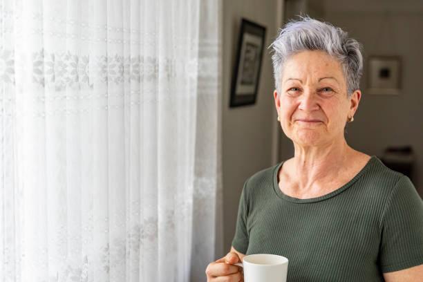 Happy Senior Woman Enjoying a Cup of Tea at Home stock photo