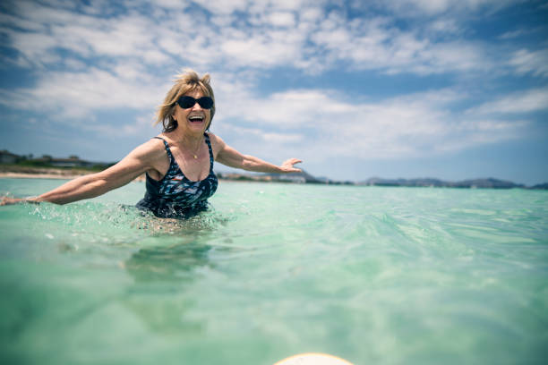 Happy senior woman enjoying beach holiday Happy senior woman enjoying beach holiday. Sunny summer day in Majorca, Spain. wading stock pictures, royalty-free photos & images