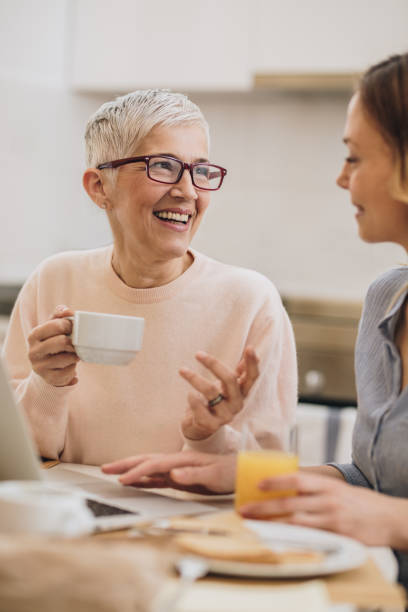 Happy senior woman enjoying in coffee time with her adult daughter. Smiling mature woman drinking coffee and talking to her daughter while using laptop at dining room. age contrast stock pictures, royalty-free photos & images