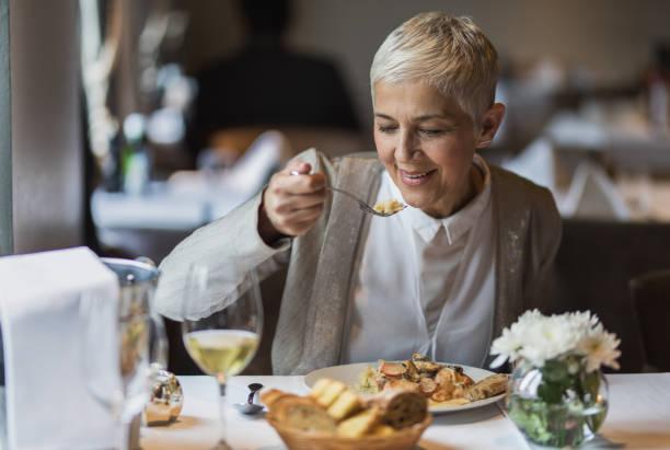 bir restoranda öğle yemeğini zevk mutlu kadın kıdemli. - yalnızca yetişkinler stok fotoğraflar ve resimler