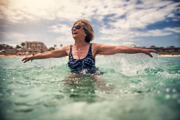 Happy senior woman enjoying sea Happy senior woman enjoying summer beach vacations. Woman is jumping in shallow sea. Nikon D850 wading stock pictures, royalty-free photos & images