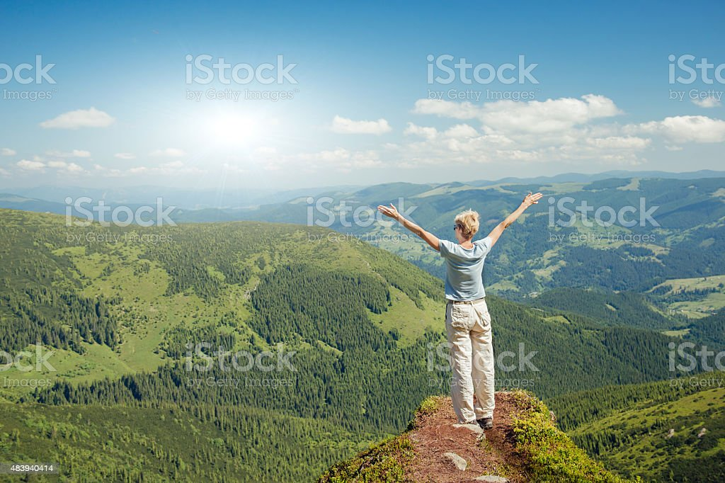 Happy senior woman enjoying the nature in the mountains stock photo