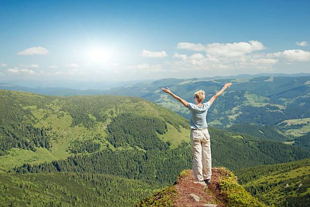 Happy senior woman enjoying the nature in the mountains stock photo