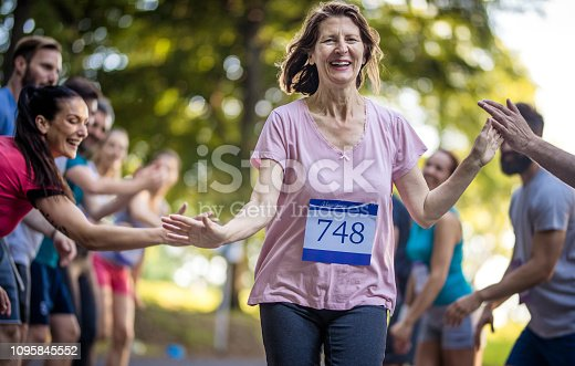 istock Happy senior woman finishing marathon race and greeting with group of supporters. 1095845552
