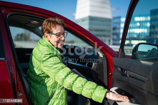 happy smiling senior woman 70 years old get in to the car closing the door of passenger side on sunny winter day on parking space, shallow focus