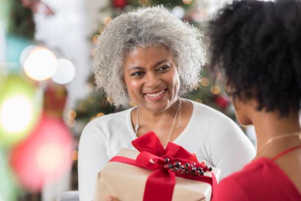 beautiful senior woman gibt tochter weihnachtsgeschenk - geschenke eltern weihnachten stock-fotos und bilder