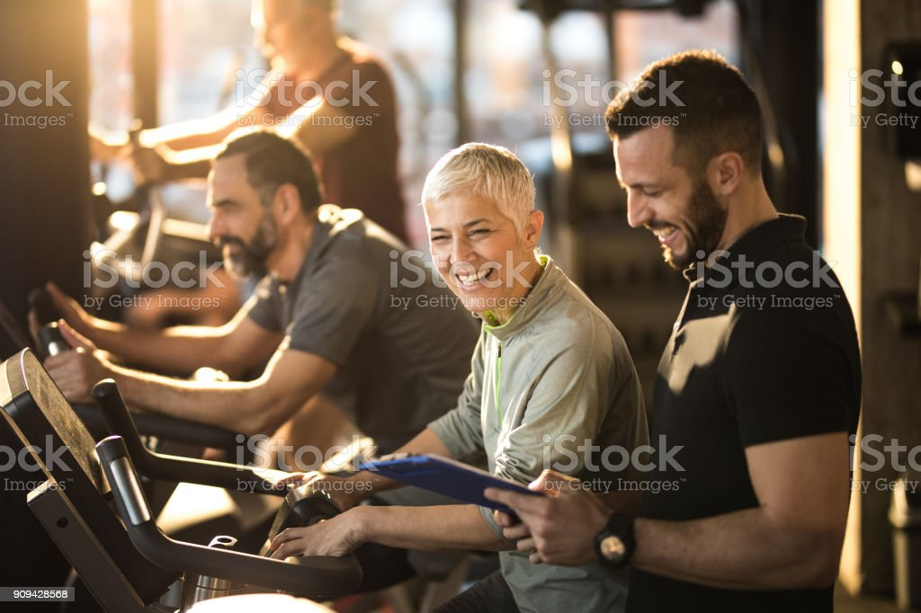 Happy senior woman having fun with her coach on spinning class in a gym. stock photo
