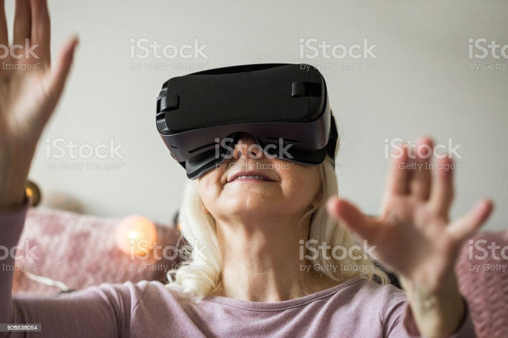 Happy senior woman having fun with vr headset stock photo