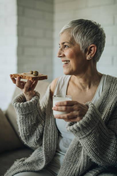 glücklich senior frau, die ihr frühstück zu hause. - oliven wohnzimmer stock-fotos und bilder