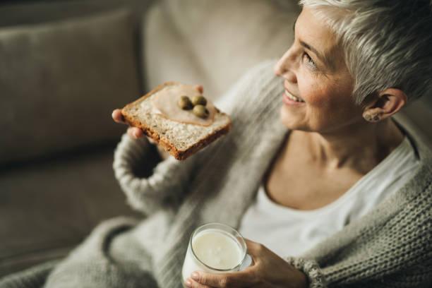 glücklich senior frau, die ihr zu hause snack. - oliven wohnzimmer stock-fotos und bilder