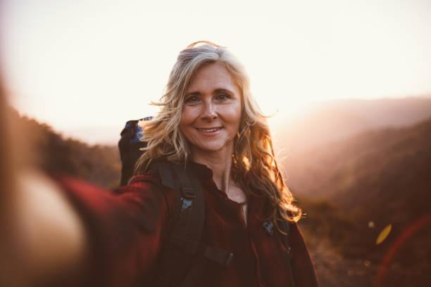 happy senior woman hiker taking a selfie on mountain edge - woman portrait forest foto e immagini stock