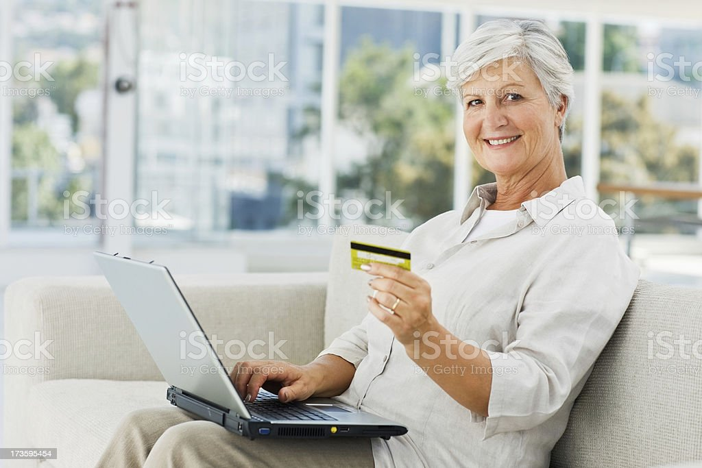 Happy senior woman holding credit card and using laptop royalty-free stock photo