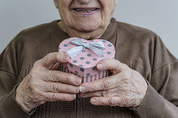 happy senior woman holding heart shaped gift - senior valentine stock photos and pictures