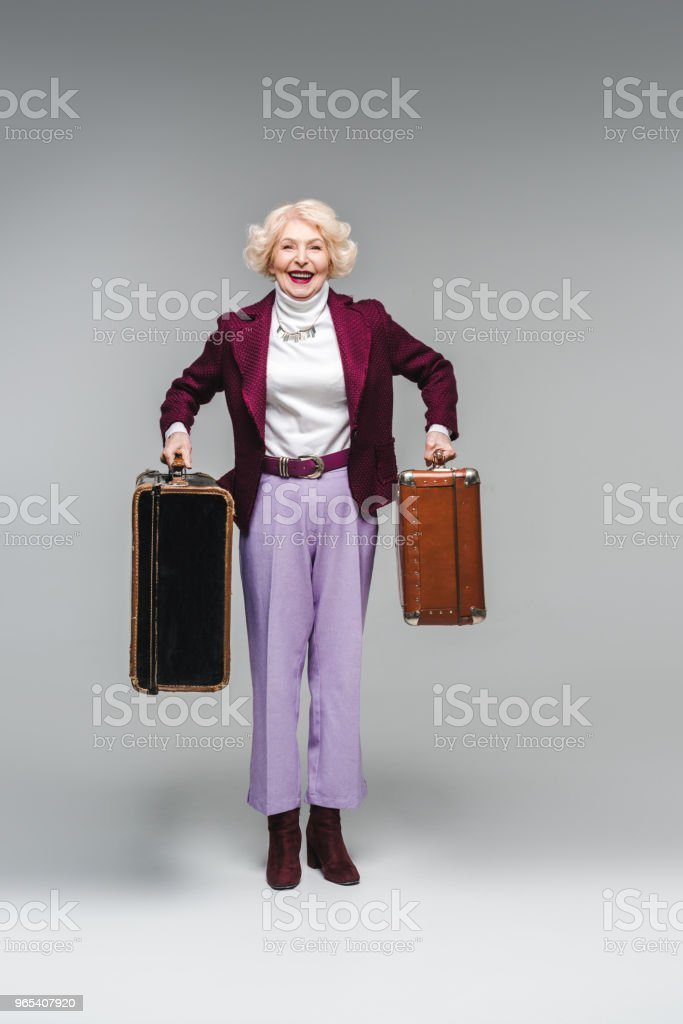 happy senior woman holding vintage suitcases and looking at camera on grey royalty-free stock photo