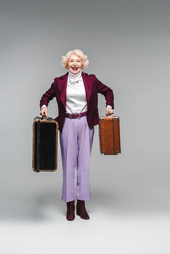 빈티지 여행 가방을 들고와 회색에 카메라 보고 행복 한 고위 여자 개체 그룹에 대한 스톡 사진 및 기타 이미지