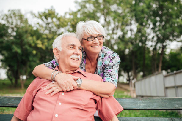 Happy senior woman hugging her husband sitting on the bench in the park Mature couple hugging while sitting in the park retirement community stock pictures, royalty-free photos & images