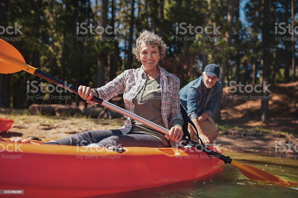 Happy senior woman in a kayak at the lake stock photo