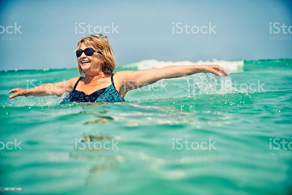 Happy senior woman in sea stock photo