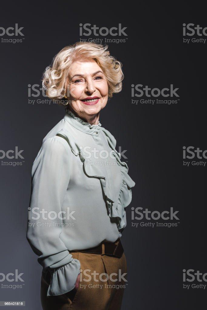 happy senior woman in stylish shirt looking at camera on dark grey royalty-free stock photo