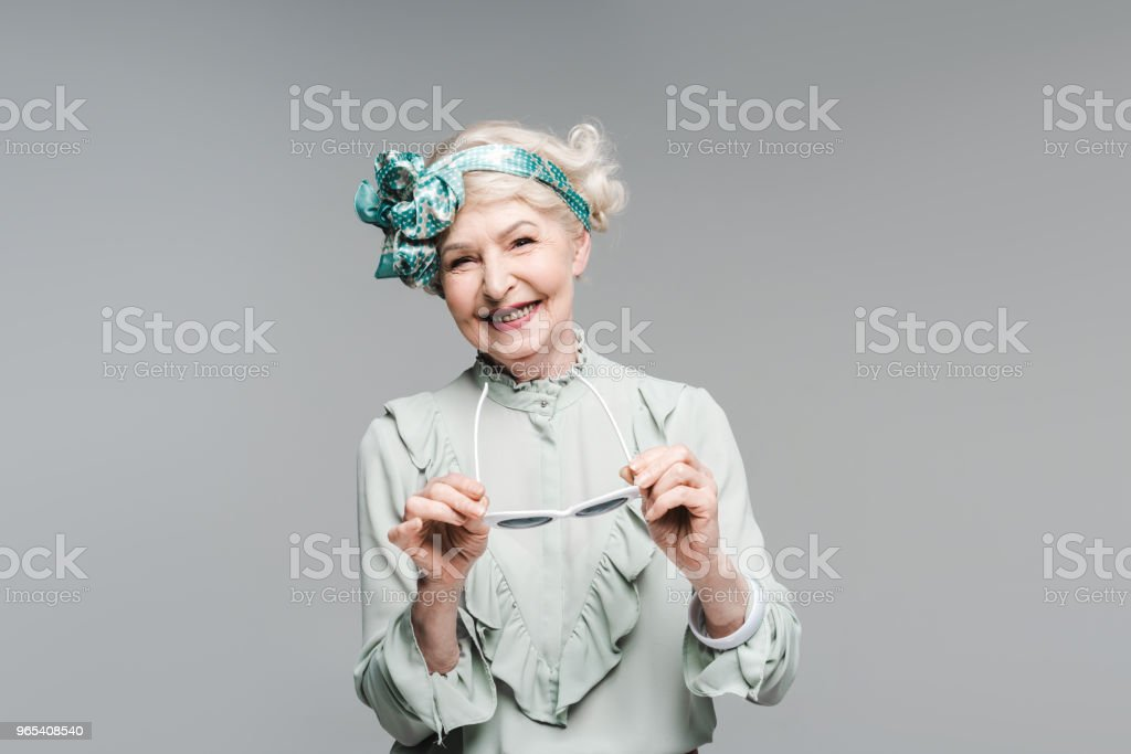 happy senior woman in stylish vintage clothes and sunglasses isolated on grey royalty-free stock photo