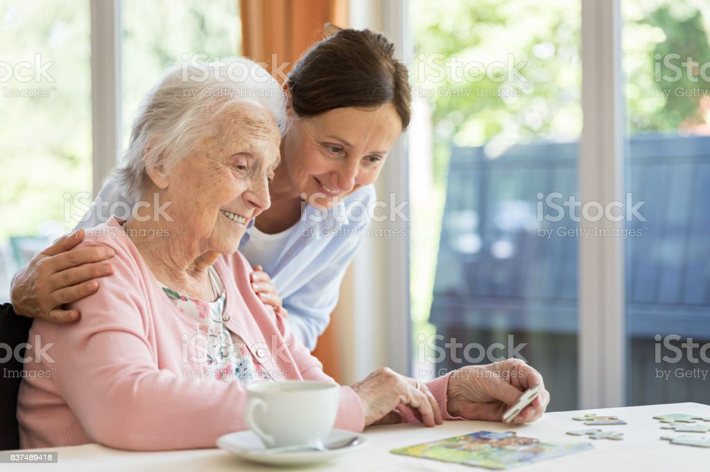 Happy senior woman in wheelchair with caregiver stock photo