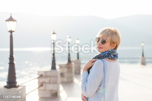 istock Happy senior woman is walking, smiling and enjoying life by winter sea. Beautiful retired female person is wearing in casual blue clothes, scarf, sunglasses. Active lifestyle of pensioner. 1157746165
