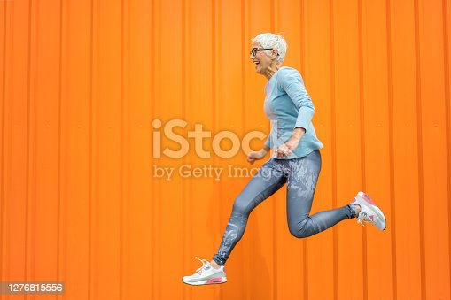 Portrait of beautiful excited mature woman with grey hair jumping . Attractive middle aged woman with beautiful smile isolated over orange background.