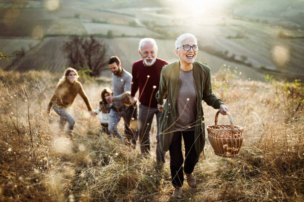 happy senior woman leading her family to perfect picnic place on the hill. - generazioni foto e immagini stock
