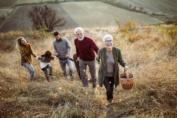 Happy senior woman leading her family to perfect picnic place on the hill. stock photo