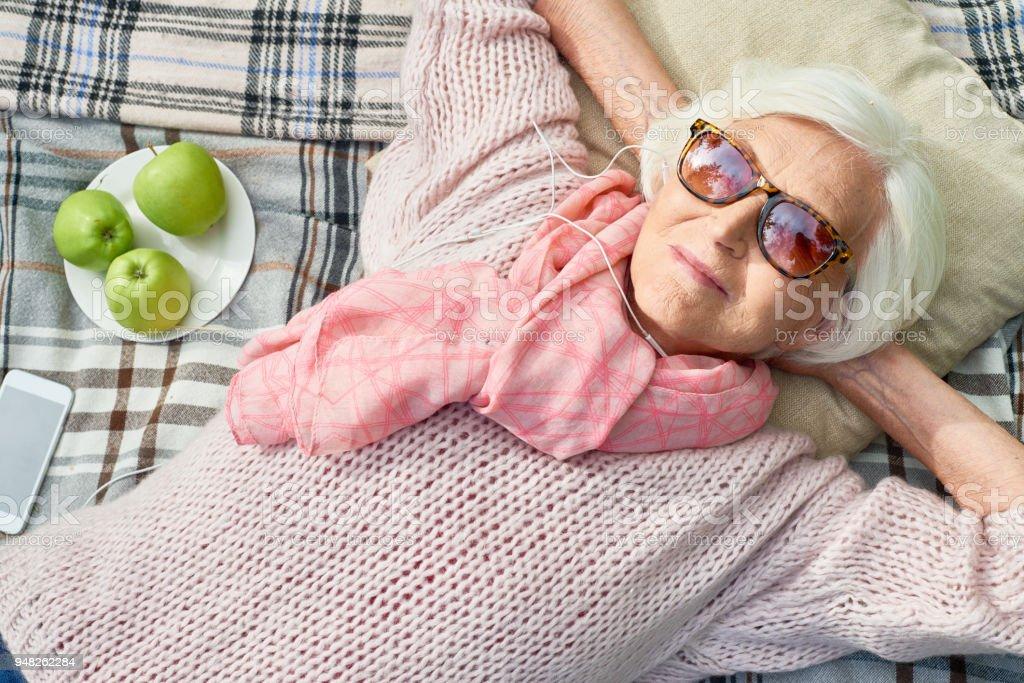 Happy Senior Woman Musikhören bei Picknick – Foto