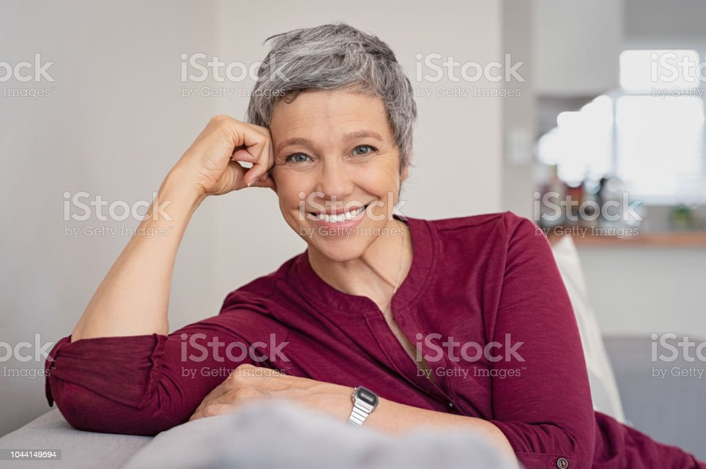 Happy senior woman on couch foto stock royalty-free