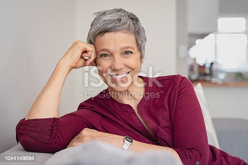 Portrait of smiling senior woman relaxing on couch at home. Happy mature woman sitting on sofa and looking at camera. Closeup of lady relaxing at home.