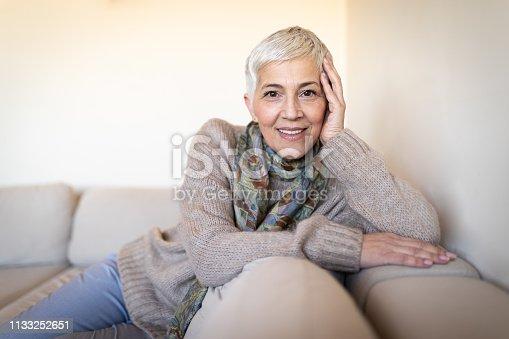 1044149594 istock photo Happy senior woman on couch 1133252651