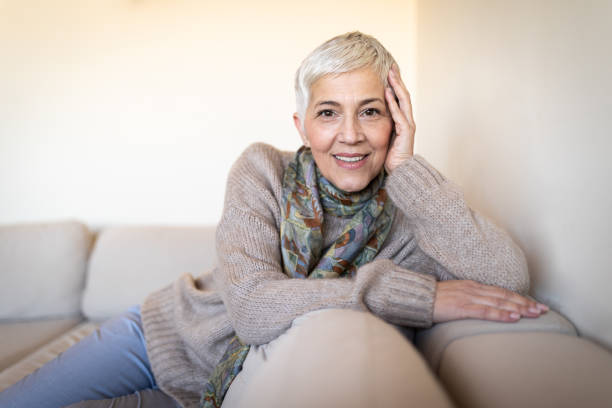 Happy senior woman on couch stock photo
