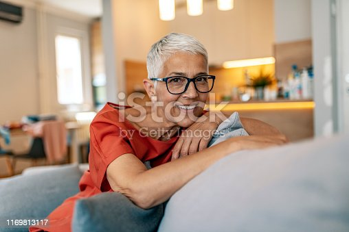 1044149594 istock photo Happy senior woman on couch 1169813117