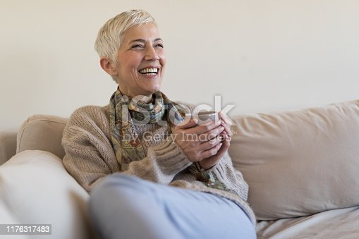 1044149594 istock photo Happy senior woman on couch 1176317483