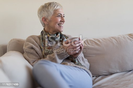 1044149594 istock photo Happy senior woman on couch 1176317499