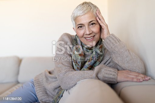 1044149594 istock photo Happy senior woman on couch 1181284120