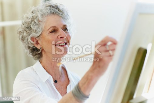 Senior woman smiling while painting on canvas
