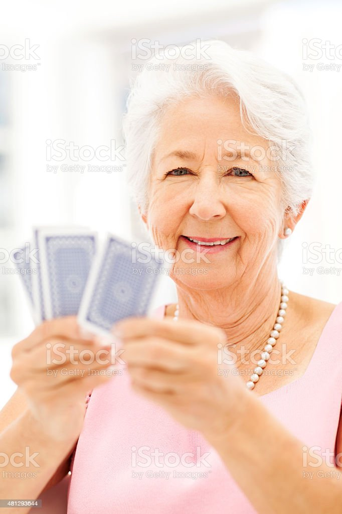 Happy Senior Woman Playing Cards stock photo